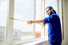 Window installation worker. Measuring window with tape royalty free stock image