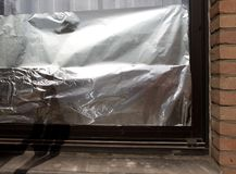 Window insulated with aluminium foil to protect house against heat wave Stock Photos
