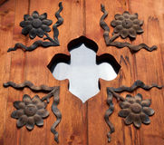 Window with iron decoration. Vintage door detail with iron flowers and small window Royalty Free Stock Images