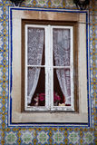 Window with lace curtains and ornate tiles Royalty Free Stock Image