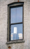 Window with Lamp and Books and Brick Building Stock Photo