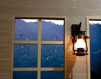 Window. The Lamp Hang near The Wood window , peer through the Window is mountain and The Birds Stock Image