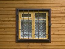 Window with a lattice. Single window with curtains behind a lattice with the lock on a wooden wall stock photos