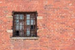 Window with lattice on brick facade. Broken window with lattice on the brick facade of an abandoned building Royalty Free Stock Photography