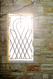 Window with a lattice. In the stone wall Royalty Free Stock Photo