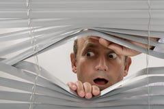 Window. Man watching something shocking through the window shutter Royalty Free Stock Photos
