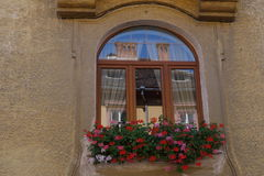 Window mirroring opposite building in Sibiu city, Romania. Old house beautiful window with flowers in Sibiu city, in Romania Stock Images