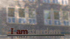 Window of moving tram with I amsterdam slogan. Slogan I amsterdam on the window of tram or bus traveling through the city stock video footage