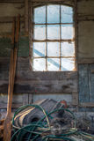 Window, oars and a mess. By a window in an old and worn building a mess lyes beneath and a pair of oars beside it Stock Photo