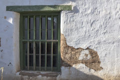Window on a old adobe building showing signs of wear and peeling Stock Photo