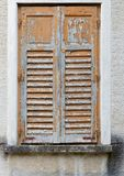 Window of old building covered by wooden blinds with peeling paint Stock Photos