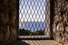 Window in old castle. Window in old castle with view to blue sea stock photos