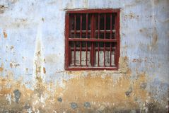 Window with bars and newspapers in an old grungy wall, Daxu, China Royalty Free Stock Photo