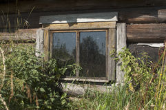 A window is old rustic home. A small window is very old rustic, abandoned, log home Royalty Free Stock Image