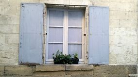 Window with blue wooden shutters in old stone house Royalty Free Stock Photography
