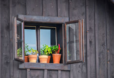 Window of an old wooden cabin with flowers Royalty Free Stock Photo