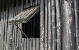 The window of the old wooden log house. On the background of wooden walls Royalty Free Stock Photo