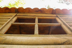 Window of the old wooden log house. With sun rays coming into Royalty Free Stock Photos