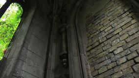 Window opening in ancient stone crypt at graveyard stock video footage