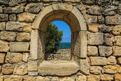 The window opening into the ancient walls of natural stone. Royalty Free Stock Photography