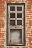 Window in an orange brick wall. Damaged window in an old orange brick wall Royalty Free Stock Images