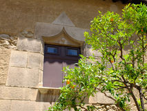 The window and the orange tree. In the Poble Espanyol the Spanish Settlement. This is the architectural open-air museum in Barcelona, Spain Stock Photo