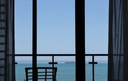 Window overlooking blue sea. Calm blue sea viewed through interior window of stylish modern house or home Stock Photo