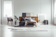 Window and paintings in bedroom. Wooden bench and grey chair near king size bed against white wall with copy space in bedroom with window and paintings royalty free stock images