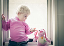 Window pane. Little girl sitting on the window pane looking at her favorite toy stock photography