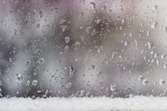 Window pane during a rain with sleet. Background from a streams and drops of water on the window pane and strip of the wet snow at the bottom during a rain with royalty free stock photography