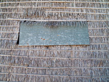 Window panel on thatch wall Stock Image