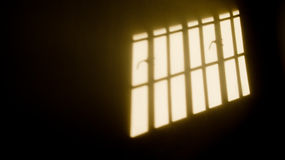 Window panes shadows. The sun shines through a high paned window in a dark room with white walls. Photo taken on November 20th, 2014 Royalty Free Stock Image