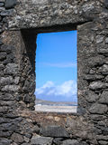 Window on Paradise II. WIndow in stacked stone wall looks out at blue sky Royalty Free Stock Photos