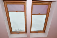 Window on a penthouse with pink rol-curtains Stock Photo