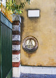 Window, pillar and sign plate. Street detailes:  round window, entrance pillar, fence and  marble sign plate on the antique  wall Stock Photography