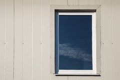 Window in plastic siding wall Stock Photo
