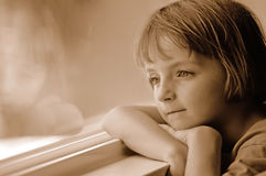 Window Portrait of Little Girl Looking Out. Portrait of little girl looking out window while daydreaming Royalty Free Stock Image