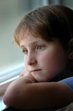 Window Portrait Young Girl Looking Out. Window Portrait of young girl with blue shirt looking out window Stock Image