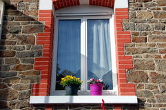 Window with potted flowers. In a stone house, France Stock Photo