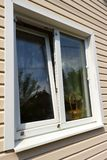 The window of a private house. Window of a private house on a background of beige siding royalty free stock photo