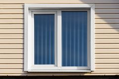 The window of a private house. Window of a private house on a background of beige siding stock photos