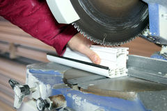 Window Profile Cutting Machine. Worker cutting PVC profile with circular saw. Selective focus Stock Photos