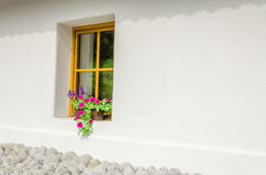 Window with purple geraniums in a small cottage Royalty Free Stock Images