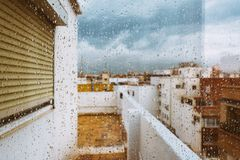 Window with raindrops on it, overlooking the terrace. stormy sky. Window with raindrops against the background, multi colored spots of the cityscape. Summer Stock Photography