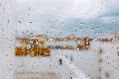 Window with raindrops on it, overlooking the terrace. stormy sky. Window with raindrops against the background, multi colored spots of the cityscape. Summer royalty free stock photo