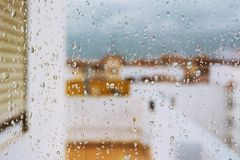 Window with raindrops on it, overlooking the terrace. stormy sky. Window with raindrops against the background, multi colored spots of the cityscape. Summer royalty free stock image
