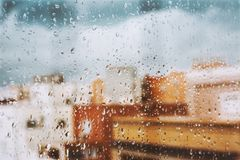 Window with raindrops on it, overlooking the terrace. stormy sky. Window with raindrops against the background, multi colored spots of the cityscape. Summer stock images