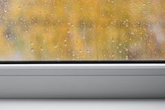 Window with raindrops and white sills, autumn background.  Royalty Free Stock Image