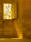 Window with rays of light. Stained Glass window with rays of golden light on stone wall Stock Image