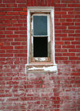 Window and Red Brick. Old window with peeling white paint in old red brick building Stock Photo